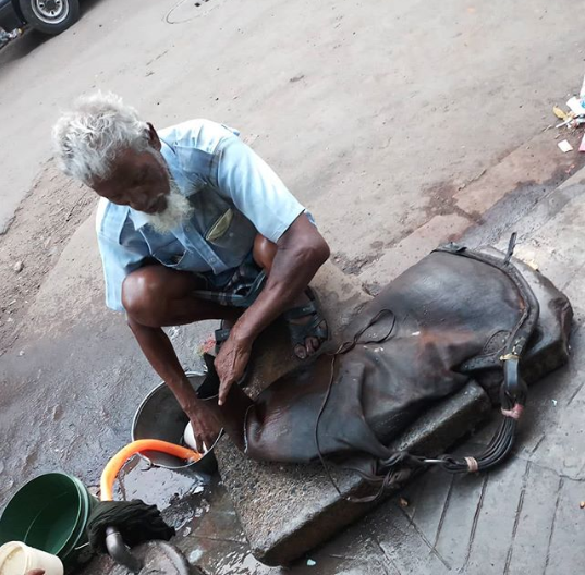 Bhishti, filling water in his goat-skin bag from a street-side tap